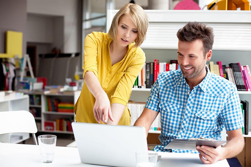 Nuri nainen ja mies keskustelevat ja tarkastelevat kannettavan tietokoneen näyttöä toimistossa.