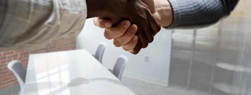 Kaksi ihmistä puristaa kättä sopimuksen merkiksi.